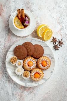 上面図白い背景の上のお茶とおいしいクッキークッキービスケット甘いケーキ茶砂糖