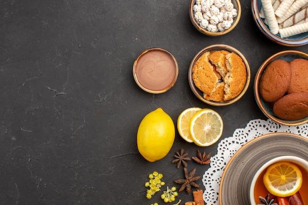 Vista dall'alto deliziosi biscotti con una tazza di tè e limone su una superficie scura biscotto dolce biscotto agli agrumi zucchero di frutta