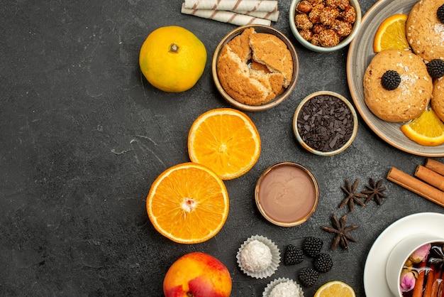 Vista dall'alto deliziosi biscotti con una tazza di tè e fette d'arancia su una torta di biscotti con biscotto al tè con superficie scura