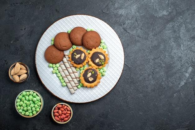 Top view delicious cookies with different candies on dark-grey background sugar biscuit sweet cake pie tea cookie