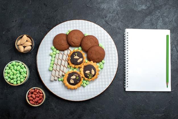 Top view delicious cookies with different candies on dark grey desk sugar biscuit sweet cake pie tea cookie