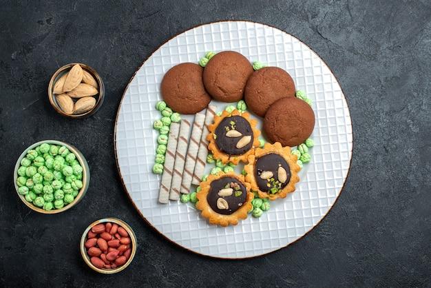 ダークグレーの背景にさまざまなキャンディーを使ったおいしいクッキーの上面図シュガービスケットスイートケーキパイティークッキー