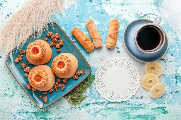 上面図乾燥パイナップルリングベーグルと青い背景のコーヒーとおいしいクッキービスケット甘い砂糖の色