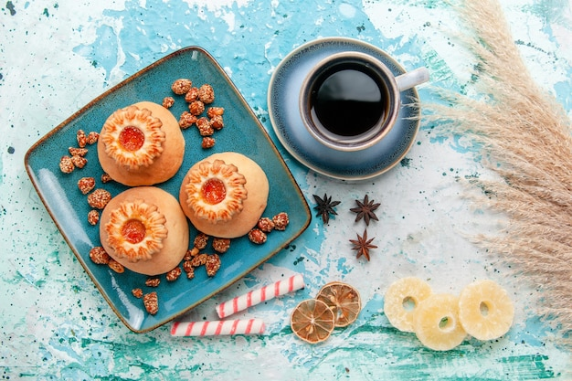 Top view delicious cookies with dried pineapple rings and coffee on blue surface cookies biscuit sweet sugar color