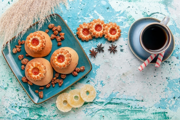 Top view delicious cookies with dried pineapple rings and coffee on light blue surface cookie biscuit sweet sugar color