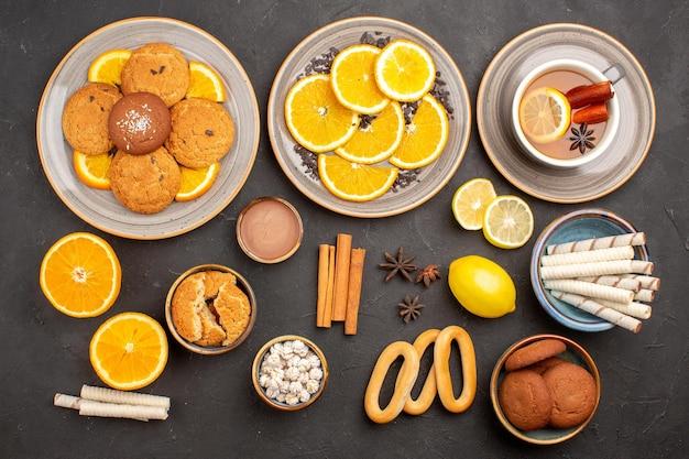 ダークサーフェスのシュガークッキーフルーツビスケットスイートに新鮮なオレンジとお茶を添えたトップビューのおいしいクッキー
