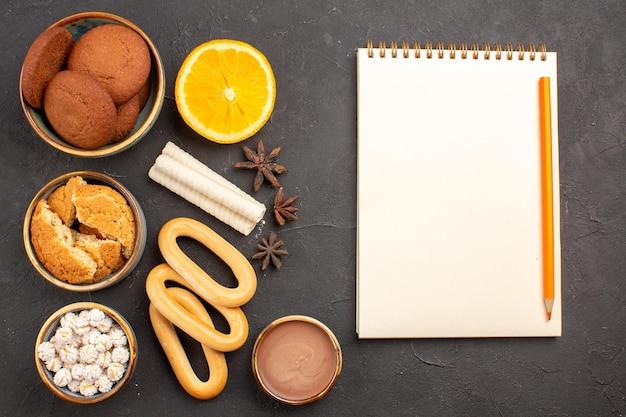 Top view delicious cookies with fresh oranges on dark surface cookies biscuit sugar cake dessert sweet