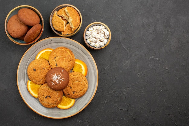 Vista dall'alto deliziosi biscotti con arance fresche a fette su sfondo scuro torta di biscotti alla frutta dolce di biscotti agli agrumi