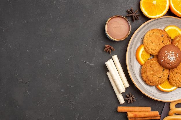 Top view delicious cookies with fresh sliced oranges on dark background sugar cookie fruit biscuit sweet