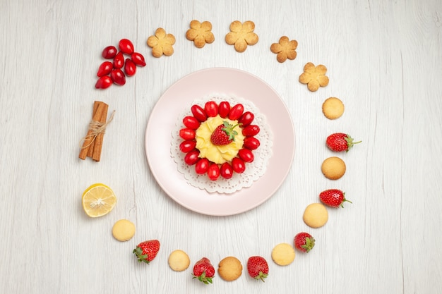 Top view delicious cookies with fruits and cake on white desk