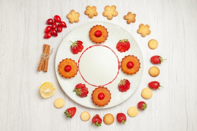 Vista dall'alto deliziosi biscotti con frutta sulla scrivania bianca