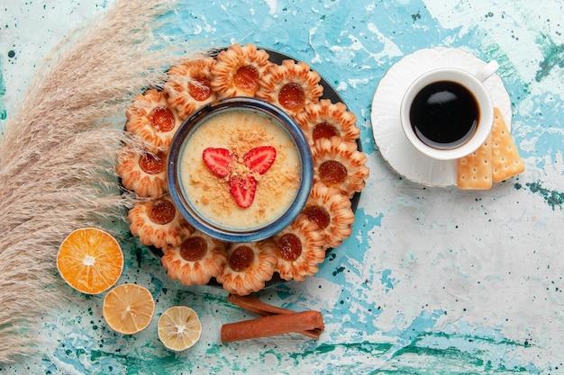 Vista dall'alto deliziosi biscotti con marmellata di caffè e dessert alla fragola sulla scrivania blu