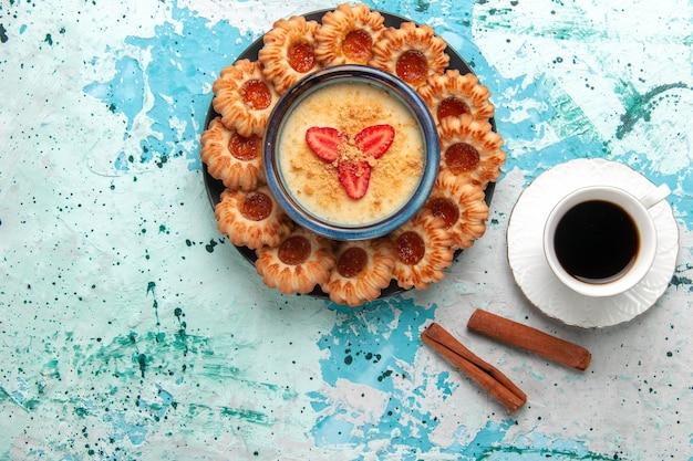 Vista dall'alto deliziosi biscotti con marmellata di caffè e dessert alla fragola sulla superficie blu