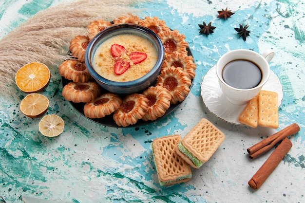 Top view delicious  cookies with jam cup of coffee and strawberry dessert on light-blue surface