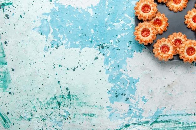 Vista dall'alto deliziosi biscotti con marmellata all'interno della banda nera sulla scrivania blu chiaro biscotto biscotto dolce zucchero colore tè