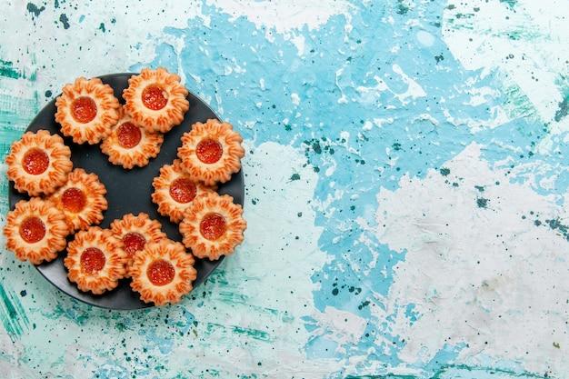 上面図青い背景の黒いプレートの中にジャムのあるおいしいクッキークッキービスケット甘い砂糖色のお茶