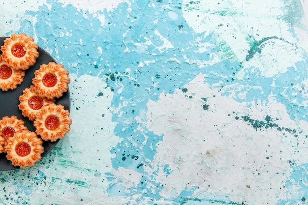 밝은 파란색 책상 쿠키 비스킷 달콤한 설탕 색 차에 검은 접시 안에 잼이있는 상위 뷰 맛있는 쿠키
