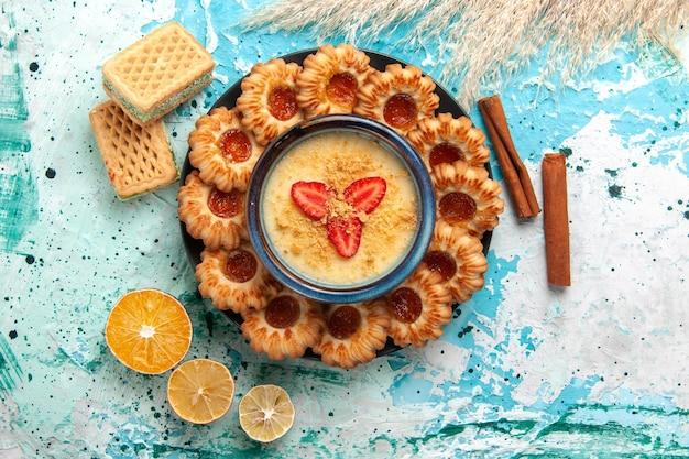 Vista dall'alto deliziosi biscotti con marmellata e dessert alla fragola sulla scrivania blu
