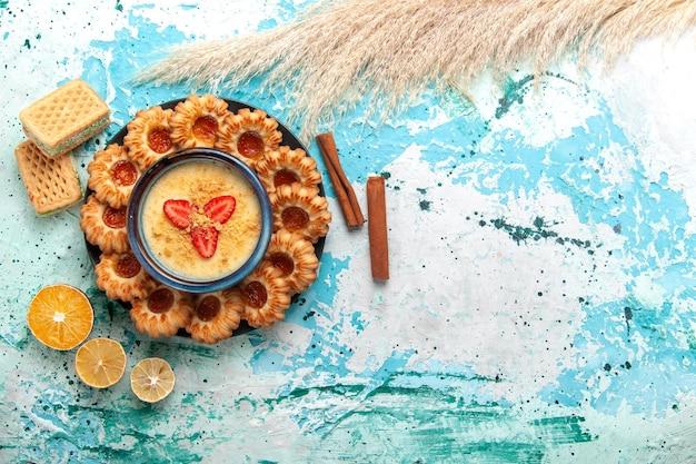 Vista dall'alto deliziosi biscotti con cialde di marmellata e dessert alla fragola sulla scrivania blu