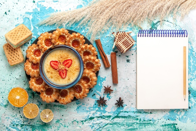Vista dall'alto deliziosi biscotti con cialde di marmellata e dessert alla fragola sulla superficie blu