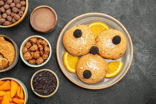 짙은 회색 배경 쿠키 비스킷 차 달콤한 케이크에 견과류와 오렌지 조각을 넣은 상위 뷰 맛있는 쿠키