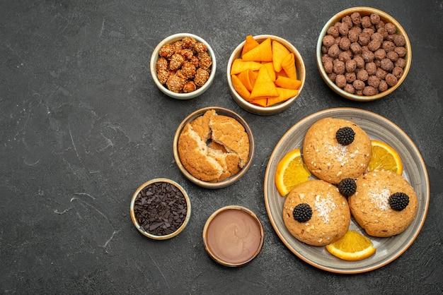 짙은 회색 배경 쿠키 비스킷 차 달콤한 케이크에 견과류와 오렌지 조각을 곁들인 맛있는 쿠키