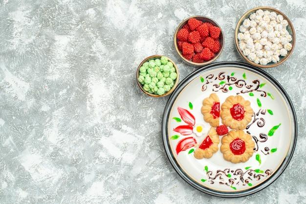 Вид сверху вкусное печенье с красным желе и конфетами на белом фоне, печенье, печенье, сладкое