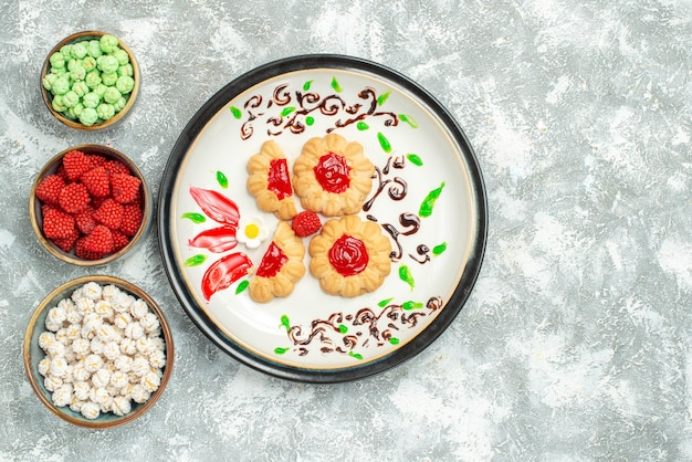 Top view delicious cookies with red jelly and candies on light white background biscuit cake cookie sweet tea