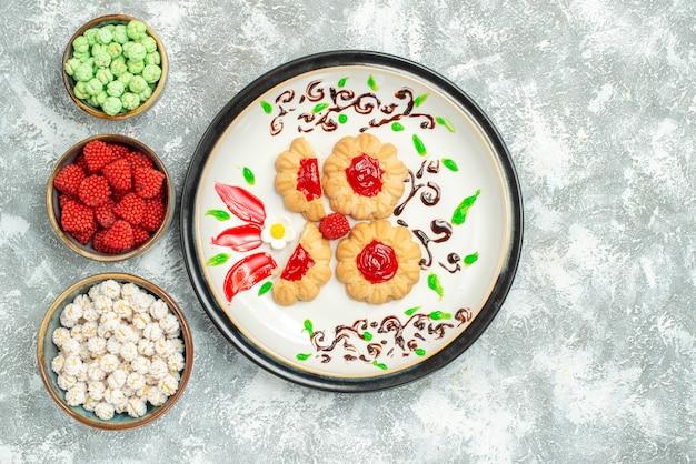 Vista dall'alto deliziosi biscotti con gelatina rossa e caramelle su sfondo bianco biscotto torta biscotto tè dolce
