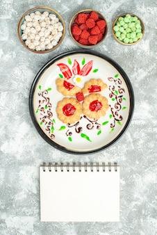 Vista dall'alto deliziosi biscotti con gelatina rossa e caramelle su sfondo bianco biscotti torta biscotto tè dolce