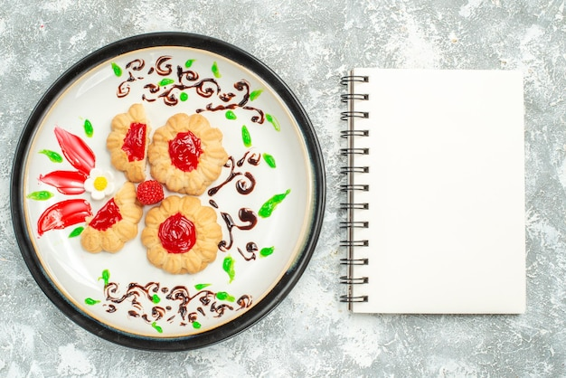 Top view delicious cookies with red jelly inside plate on light white background sugar cake cookie sweet tea