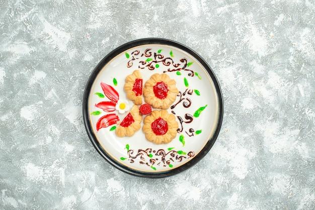 흰색 배경에 접시 안에 빨간 젤리와 상위 뷰 맛있는 쿠키 케이크 쿠키 달콤한 차