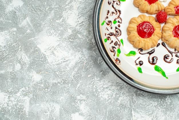 흰색 배경에 접시 안에 빨간 젤리와 상위 뷰 맛있는 쿠키 설탕 비스킷 케이크 쿠키 달콤한 차