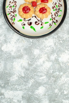 上面図白い背景の上のプレートの中に赤いゼリーとおいしいクッキーシュガービスケットケーキクッキースウィートティー