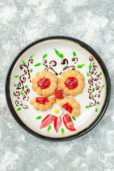 Vista dall'alto deliziosi biscotti con gelatina rossa all'interno del piatto su sfondo bianco torta biscotto tè dolce