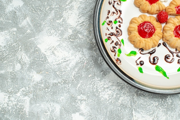 Top view delicious cookies with red jelly inside plate on the white background sugar biscuit cake cookie sweet tea