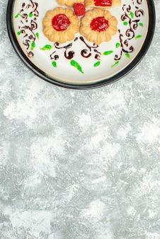 Vista dall'alto deliziosi biscotti con gelatina rossa all'interno del piatto su sfondo bianco zucchero biscotto torta biscotto tè dolce