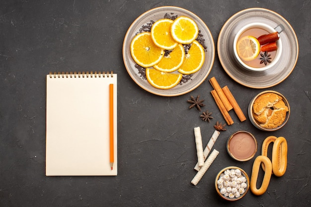 Вид сверху вкусного печенья с нарезанными апельсинами и чашкой чая на темном фоне сахарное печенье фруктовое сладкое печенье