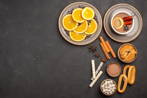 Top view delicious cookies with sliced oranges and cup of tea on a dark background sugar cookie fruit sweet biscuit