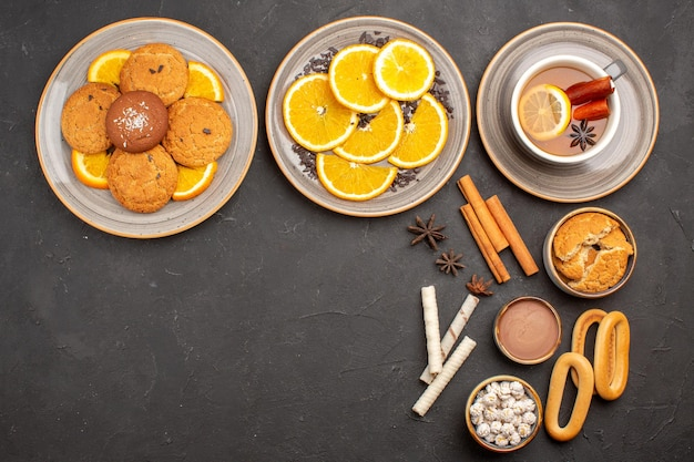 Top view delicious cookies with sliced oranges and cup of tea on dark background sugar cookie fruit sweet biscuit