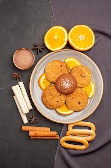 Вид сверху вкусное печенье с нарезанными апельсинами на темном фоне сахарное печенье десертное бисквитное сладкое