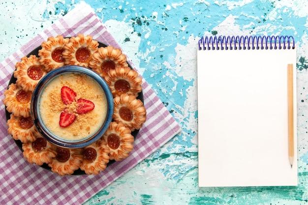 Vista dall'alto deliziosi biscotti con dessert alla fragola e blocco note su superficie blu