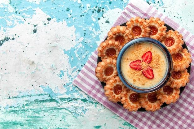 青い表面にイチゴのデザートが付いた上面図のおいしいクッキー
