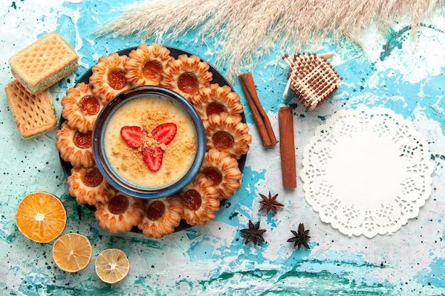青い机の上にワッフルとイチゴのデザートとトップビューのおいしいクッキー