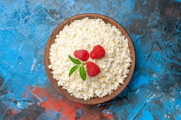 Вид сверху вкусный творог со свежей малиной на синем фоне здоровье белый цвет ягоды фото фрукты