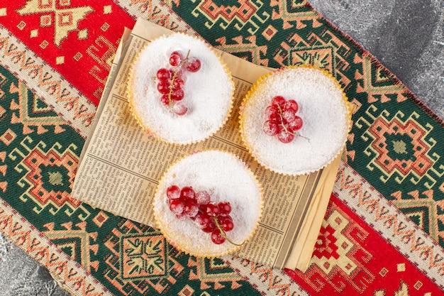 Vista dall'alto deliziose torte di mirtilli rossi con mirtilli rossi su pezzi di zucchero superiori e zucchero cuocere biscotti in polvere sfondo chiaro