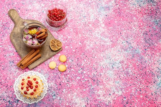 Вид сверху вкусного кремового торта с чашкой чая с корицей и красной клюквой на яркой поверхности сахарного сладкого чая