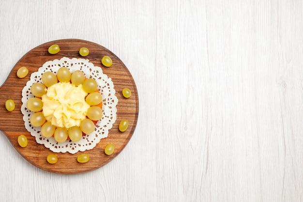 흰색 책상 과일 디저트 케이크 비스킷 파이에 녹색 포도를 곁들인 맛있는 크림 케이크