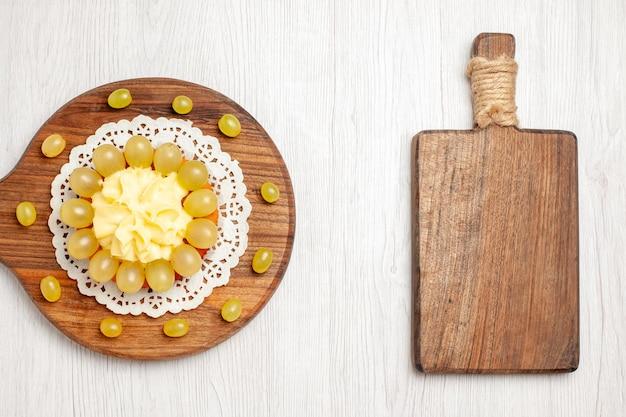 흰색 책상 과일 디저트 케이크 비스킷 파이 쿠키에 녹색 포도를 넣은 상위 뷰 맛있는 크림 케이크