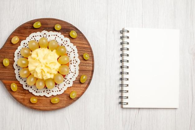 Vista dall'alto deliziosa torta alla crema con uva verde su pavimento bianco torta di frutta dolce biscotto piet
